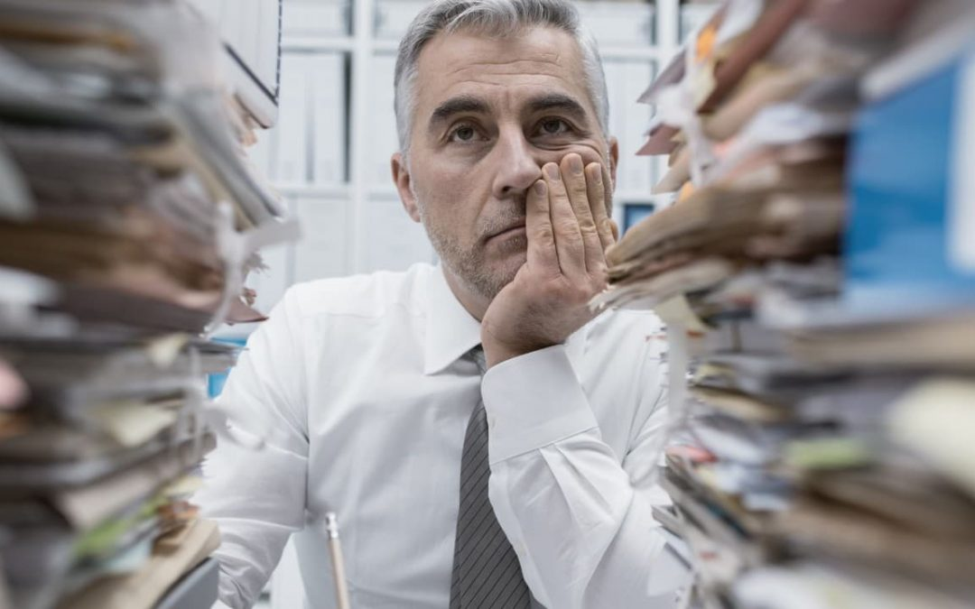 Stressed ceo with stack of papers